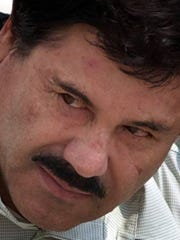 """In this Feb. 22, 2014, file photo, Joaquin """"El Chapo"""" Guzman is escorted to a helicopter by Mexican navy marines in Mexico City, Mexico."""