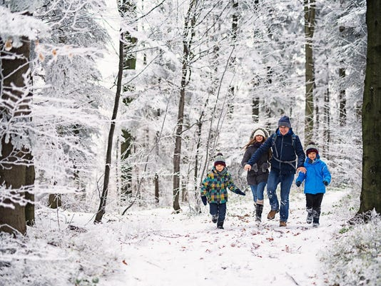 Father with kids running in beautiful winter forest