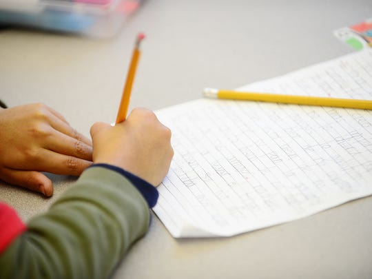 Students work on a writing exercise during a first