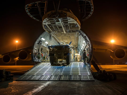 Airmen from the 9th Airlift Squadron and 455th Expeditionary Aerial Port Squadron with Marines from the Marine Expeditionary Brigade load vehicles into a C-5M Super Galaxy on Oct. 6 at Camp Bastion, Afghanistan.