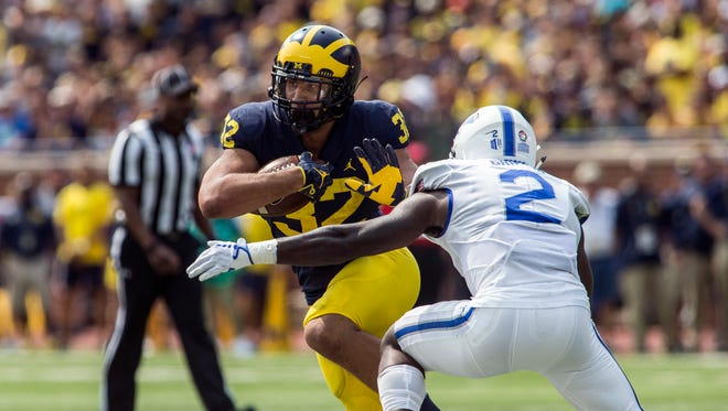 Michigan running back Ty Isaac rushes against Air Force defensive back Marquis Griffin in the second quarter in Ann Arbor, Saturday, Sept. 16, 2017.