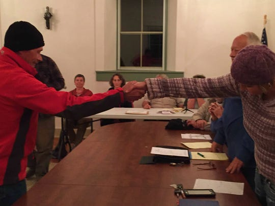 Daniel Snyder and Danyale Blackmore shake hands once  the Virgin Town Council decision was made by coin toss Monday night putting Snyder in the vacant seat.