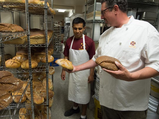 Keith Irwin, right, President of Old World Breads, and Roni Ramirez, production manager, look at freshly baked organic whole wheat sour dough with local grains and white sour dough bread at their bakery in Lewes.