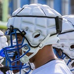 MTSU offensive linemen wearing the helmet covers Thursday.
