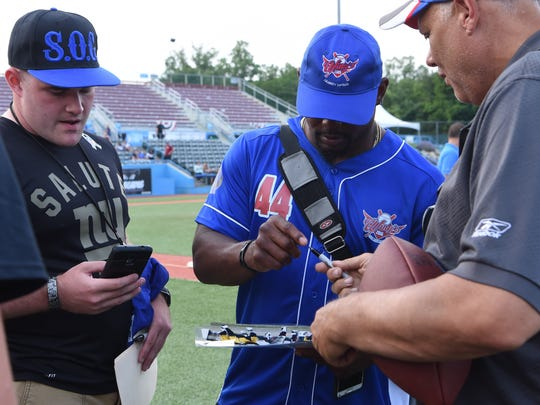 Former New York Giant Ahmad Bradshaw signs autographs for fans before a charity softball game at Dutchess Stadium on Monday.