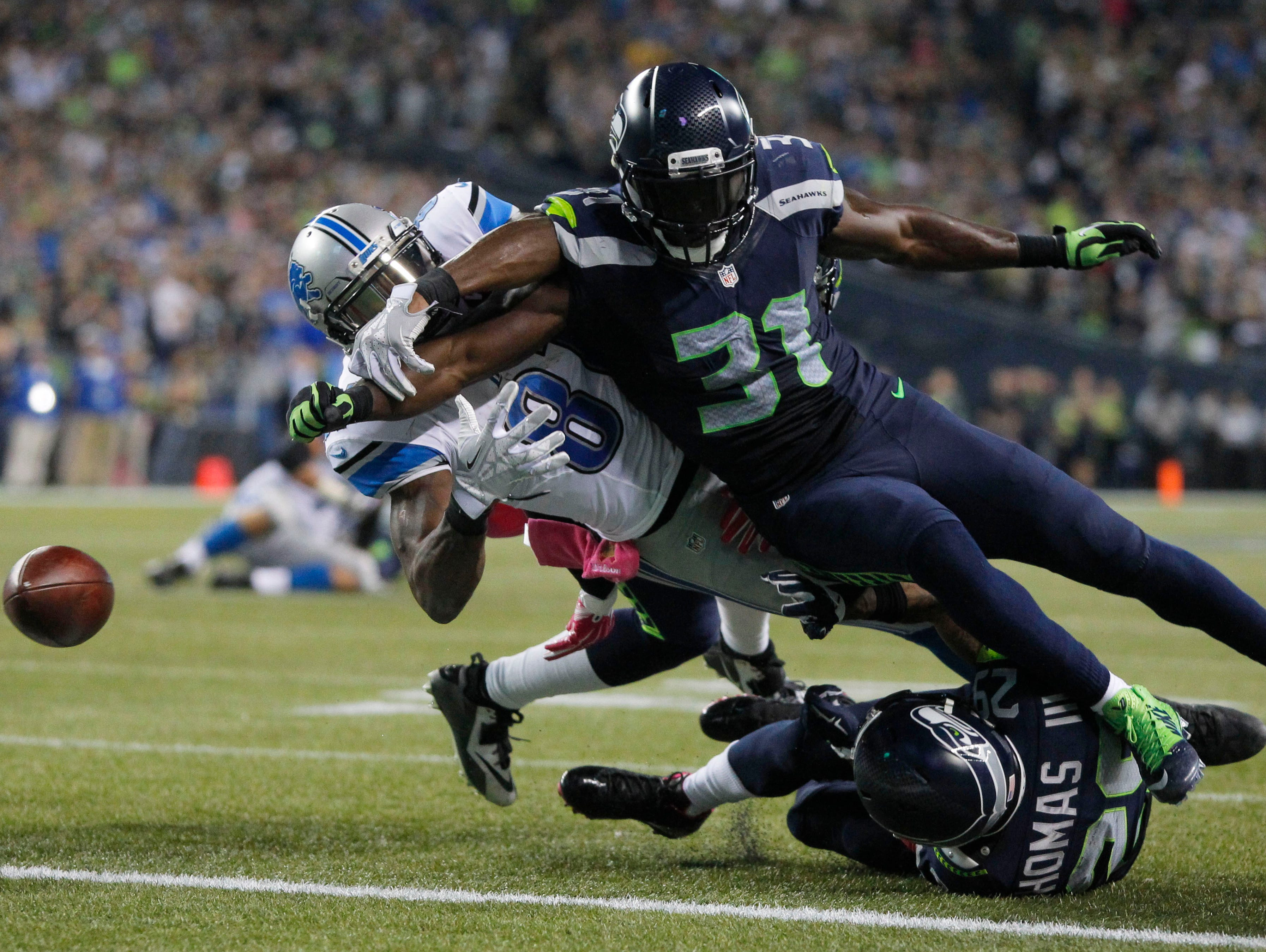 Seattle Seahawks strong safety Kam Chancellor (31) forces a fumble by Detroit Lions wide receiver Calvin Johnson (81) during the fourth quarter at CenturyLink Field.