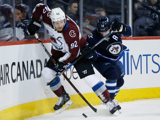 Colorado Avalanche's Gabriel Landeskog (92) and Winnipeg Jets' Bryan Little (18) fight for possession during the second period of an NHL hockey game Saturday, Feb. 3, 2018, in Winnipeg, Manitoba. (John Woods/The Canadian Press via AP)