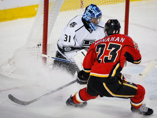 Los Angeles Kings goalie Ben Bishop, left, stops a shot from Calgary Flames' Sean Monahan during first period NHL hockey action in Calgary, Alberta, Tuesday, Feb. 28, 2017. (Jeff McIntosh/The Canadian Press via AP)