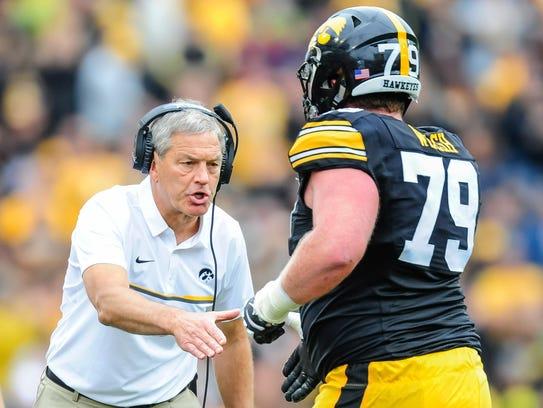 Iowa coach Kirk Ferentz greets offensive lineman Sean