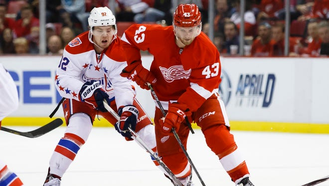 Detroit Red Wings center Darren Helm (43) skates with the puck defended by Washington Capitals center Evgeny Kuznetsov (92) in the third period at Joe Louis Arena.