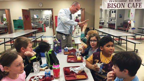 Principal Adam Cripps visits with students during lunch