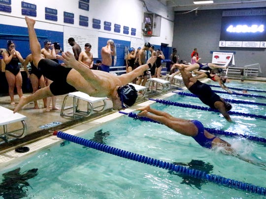 La Vergne's Isaac Morales dives into the pool with others from the block during swim practice on Wednesday, Jan. 24, 2018, at La Vergne.