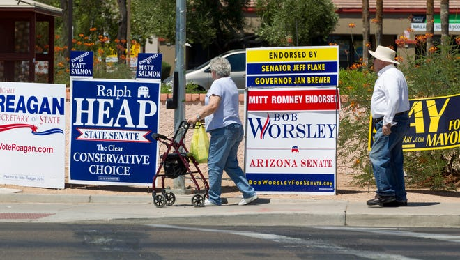 Mesa residents, Denis LeBlanc with his wife Esther crosses the intersection of Brown Road and Mesa Drive where political campaign signs cluttered at the corner on Friday August 8, 2014.
