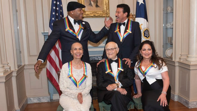Front row from left, 2017 Kennedy Center Honorees Carmen de Lavallade, Norman Lear, and Gloria Estefan, back row from left, LL Cool J and Lionel Richie celebrate following the State Department dinner for the Kennedy Center Honors, Dec. 2, 2017, in Washington.