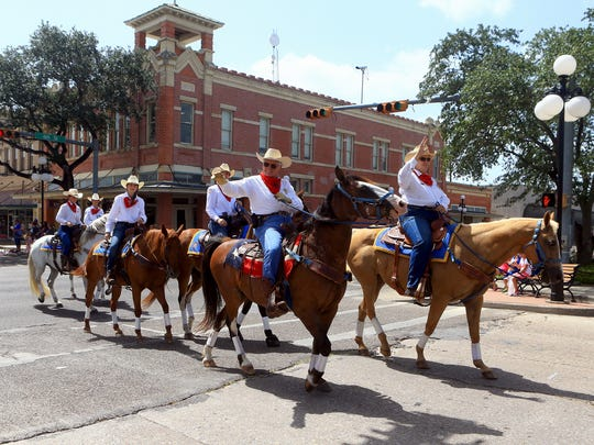 Cowboys ride in town as they wave at a crowd during