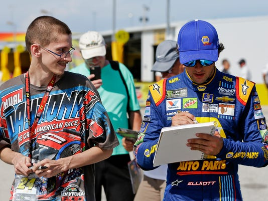 Chase Elliott, right, signs an autograph for a fan in the garage area before NASCAR Cup auto racing practice at Daytona International Speedway, Thursday, June 29, 2017, in Daytona Beach, Fla. (AP Photo/John Raoux)