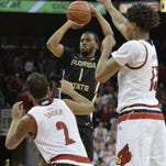 Florida State Seminoles guard Devon Bookert shoots against Louisville Cardinals guard Quentin Snider and forward Raymond Spalding during the first half of action Wednesday night at KFC Yum! Center.