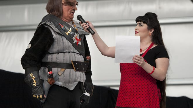 """Kaci Hansen, right, introduces Mark Vaughan of Madera Ranchos as """"Kraam from the House of Baug"""" in the costume contest during the first Tulare Sci-Fi Con at the International Agri-Center in Tulare on Saturday, March 29, 2014."""
