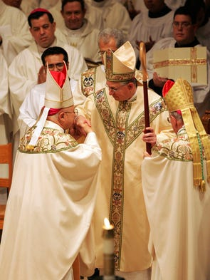 Archbishop Emeritus Patrick Flores, left, kisses the