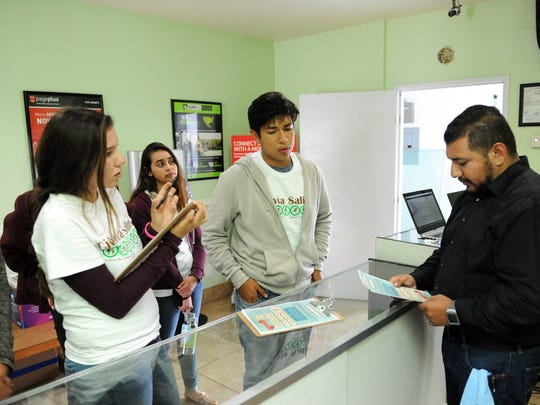 Youth from Ciclov'ía talk with Mobile Tech Shop owner Cristian Farfan about the event coming up on October 9th.