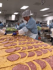 Employees of North Carolina-based MG Foods Inc. prepare food items for distribution to the company's clients. MG Foods is considering expanding into Melbourne, creating 95 jobs over the next three years.