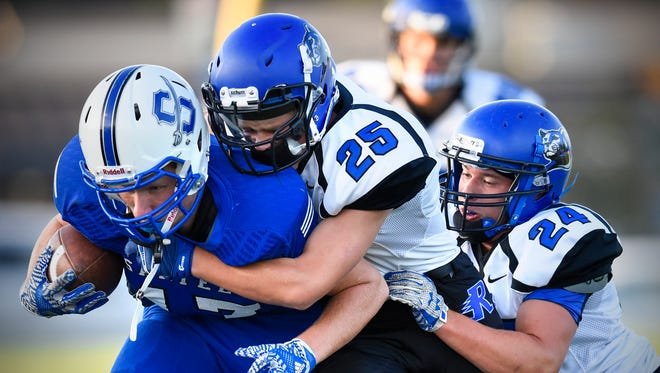 Sartell's Jared Freeman is tackled by Alec Camarote (25) and Jack Kammers (24) of Rogers during the first half of the Friday, Sept. 2, game in Sartell.