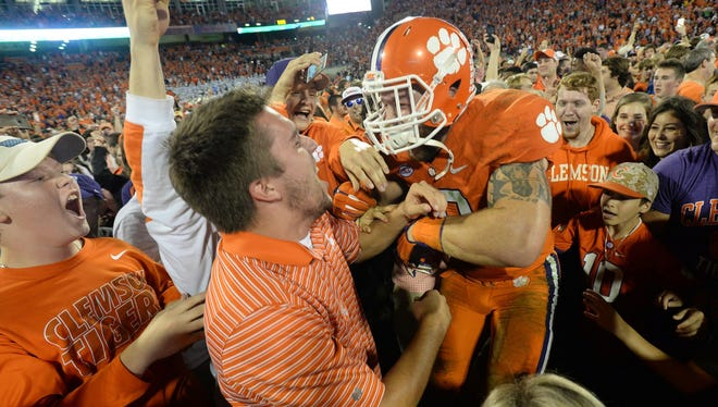 Clemson fans and players celebrate in Death Valley after a victory