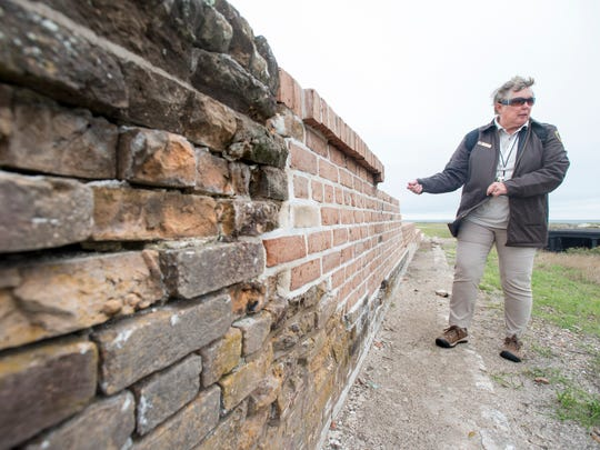Park volunteer Anne Weeks points out some of the recent preservation work at Fort Pickens at the Gulf Islands National Seashore on Tuesday, March 6, 2018.