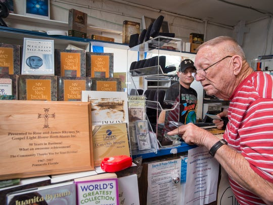 Jim Rhymes, left, looks on as H.L. Gentry looks over rings for sale at the Gospel Lighthouse Bible Book Center on Navy Boulevard in Pensacola on Friday, May 11, 2018.  The bookstore owned by Jim's family is celebrating its 50th anniversary.