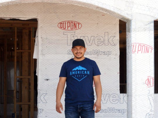 Miguel Cabral, a custodian at Columbus Elementary School, stands in front of the home he is helping build.