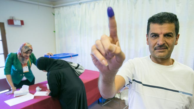 Najah Alomara holds up his inked finger after voting in the Iraqi Elections in Phoenix on Monday, April 28, 2014.