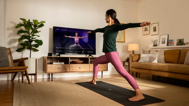A woman exercises while streaming Peloton content on a TV.