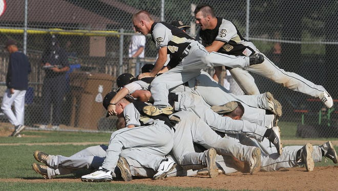 Franklin players dogpile near the pitcher's mound after winning the 2011 state summer baseball title.