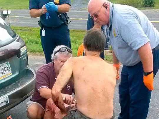 Frederick County, Va., fire and rescue workers and citizens treat Steven Krichbaum and his dog, Henry, in Middletown, Va., after that were attacked by a bear Thursday Aug. 21, 2014 in the George Washington National Forest in Hardy County, W.Va  Krichbaum and his dog were able to drive to Richard's Fruit Market near Middletown, where they sought help.  Krichbaum is in critical condition in the Winchester Medical Center and Henry was taken to an emergency veterinary hospital. (AP Photo/The Winchester Star, Eddie Richard)