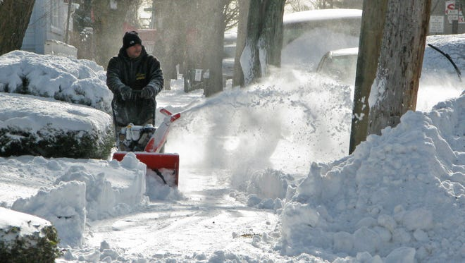 A man clears a sidewalk in the Bronx on Jan. 3, 2014, in New York.  Dubbed Winter Storm Hercules by the Weather Channel, it was one of the more memorable storms of the brutal winter.