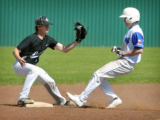 Windthorst baserunner Maclain Bowen was safe at second as Archer City shortstop Morgan Mobley takes the throw during Tuesday's game in Windthorst. The Trojans defeated the Wildcats, 11-1.