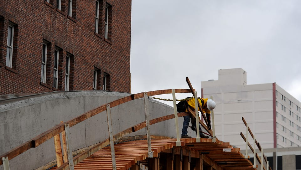 A worker is seen constructing one of the arches for