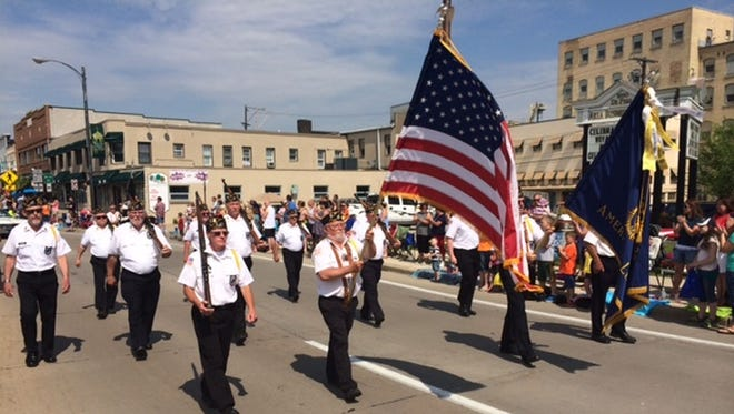 An American Legion honor guard walks on Main Avenue in downtown De Pere during the 2014 De Pere Kiwanis Memorial Day Parade.