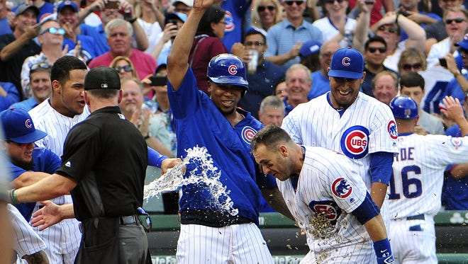 The Chicago Cubs celebrate Friday after catcher Miguel Montero (47) lifted the team to a walk-off win.