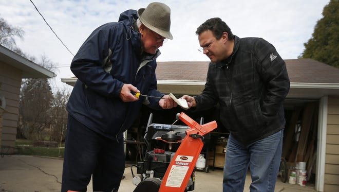 Carl Kosiorek and his son, Jeff, tune up a snowblower in Appleton on Nov. 24.