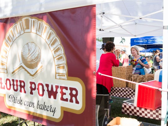 A women stops by the Flour Power booth to check out and talk about the baked goods during her time at the Franklin Street Bazaar on Saturday afternoon.