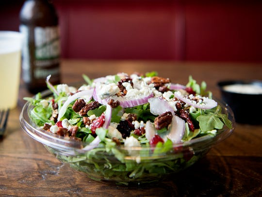 Pi Squared offers more than just pizza, such as their arugala salad topped with craisins, red onion, candied pecans, and blue cheese crumbles.