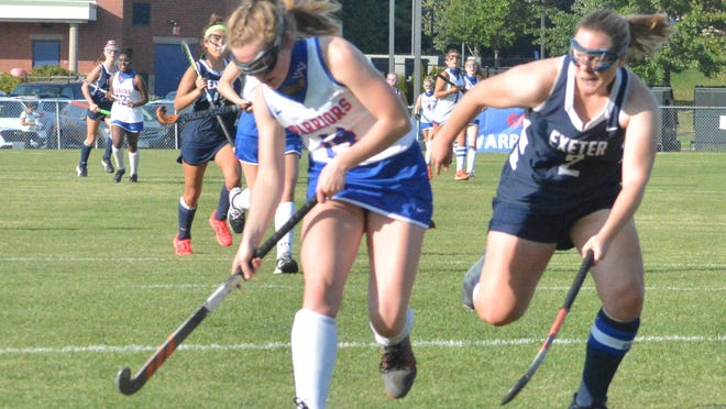 Winnacunnet's Carolyn Thompson, left, prepares to take a shot on goal as Exeter's Alida Oak defends during Wednesday's Division I field hockey game in Hampton.