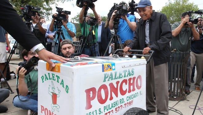 In this photo taken Sept. 21, 2016, a grateful Fidencio Sanchez pushes his paletas cart one last time before a group of of media.