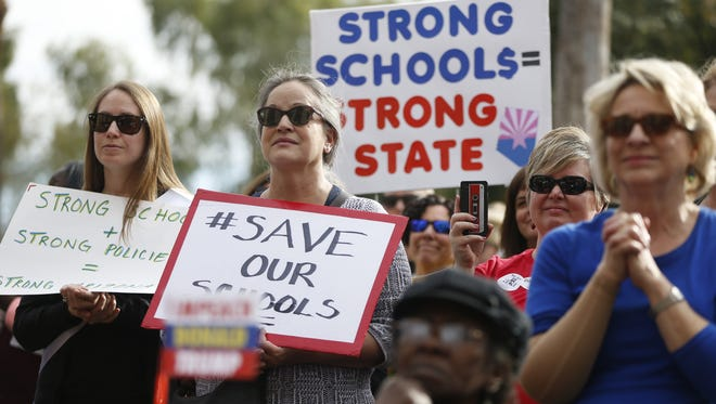 People listen to speaker Jevin Hodge during Save Our Schools rally and march outside the State Capitol on Jan. 6, 2018 in Phoenix.