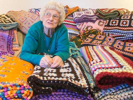 Surrounded by 30 afghans she crocheted, Janet Clark