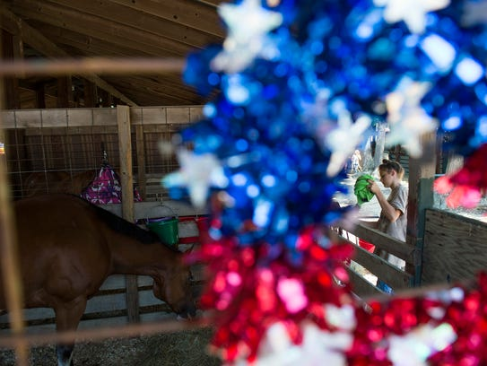 Ashley Presgraves, 12, tends to her horse Julie Tuesday,