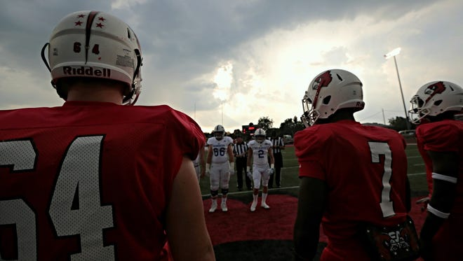 Colerain and St. X players wait out a rain delay before officials decided to postpone the game.