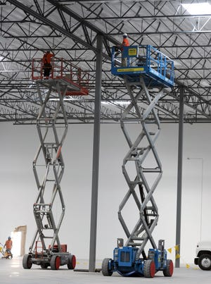Using lifts to reach the 40-foot ceiling, workers on Thursday prepare a building at the Tahoe Reno Industrial Center.