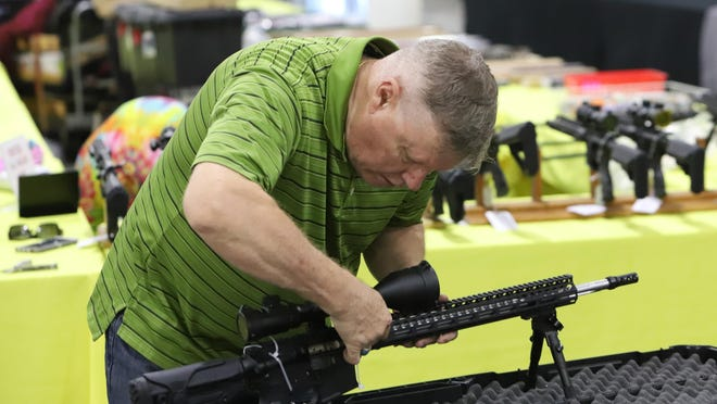 Tim Taconi with A-TAC Arms in Colorado sets up one of the company's production rifles for display, Friday, Aug. 28, for the Fort Smith Gun and Knife Show Saturday and Sunday at the Kay Rodgers Park Expo Center. Sponsored by High Caliber Radio, the event features ammo, pistols, rifles as well as vendors with all accessories. Open 9 a.m. to 5 p.m. on Saturday, and 9 a.m. to 4 p.m. on Sunday, with two-day adult admission costing $10 and children under 10-years-old attending for free with paid adult. Bring a firearm or show your concealed-carry permit, military or veteran I.D. and get $1 off.
